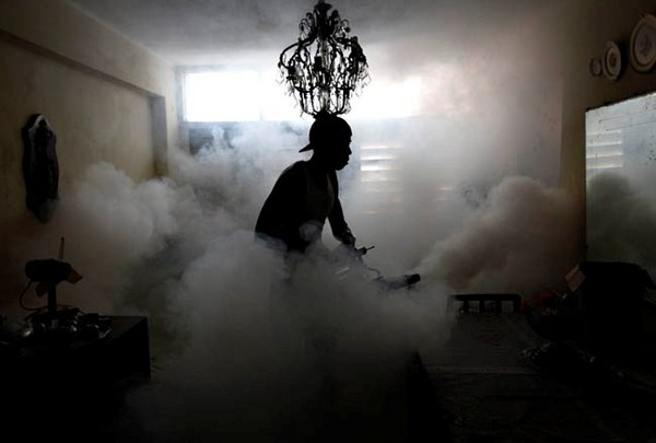 A member of a fumigation brigade sprays a home in Havana November 2, 2009. Cuba conducts regular fumigation inside homes to check the spread of dengue, a mosquito-transmitted virus that causes a fever which can be deadly. REUTERS/Desmond Boylan (CUBA HEALTH SOCIETY)