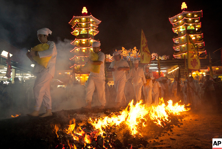 Malaysian ethnic Chinese walk barefoot over burning coals on the final day of the Nine Emperor Gods festival at a temple in Kuala Lumpur, Malaysia, Wednesday, Oct. 5, 2011. The men have abstained from meat for the past nine days in order to purify their bodies in preparation for this painful ritual, in which women are barred from participating. (AP Photo/Vincent Thian)
