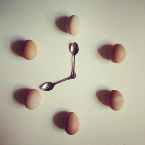 Chicken eggs and two teaspoons arranged in form of clock face