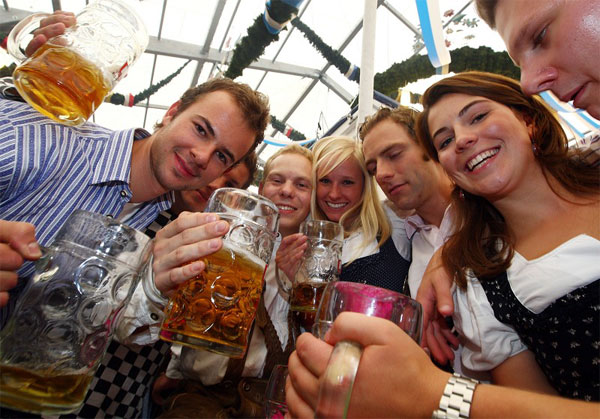 MUNICH, GERMANY - SEPTEMBER 20: Young people enjoy drinking beer at the Schottenhamel beer tent during day 1 of the Oktoberfest beer festival on September 20, 2008 in Munich, Germany. The Oktoberfest is seen as the biggest beer festival worldwide. (Photo by Johannes Simon/Getty Images)