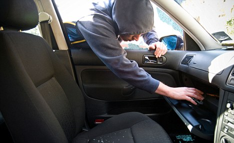 BHTXM4 A young man stealing from the glove compartment of a car