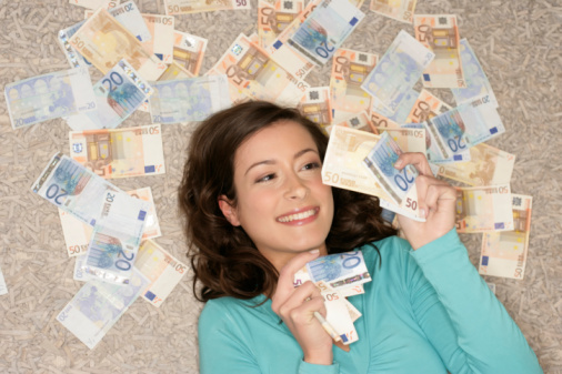 Young woman lying on the floor, surrounded by banknotes