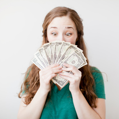 Excited young woman holding fan made up from us dollar banknotes