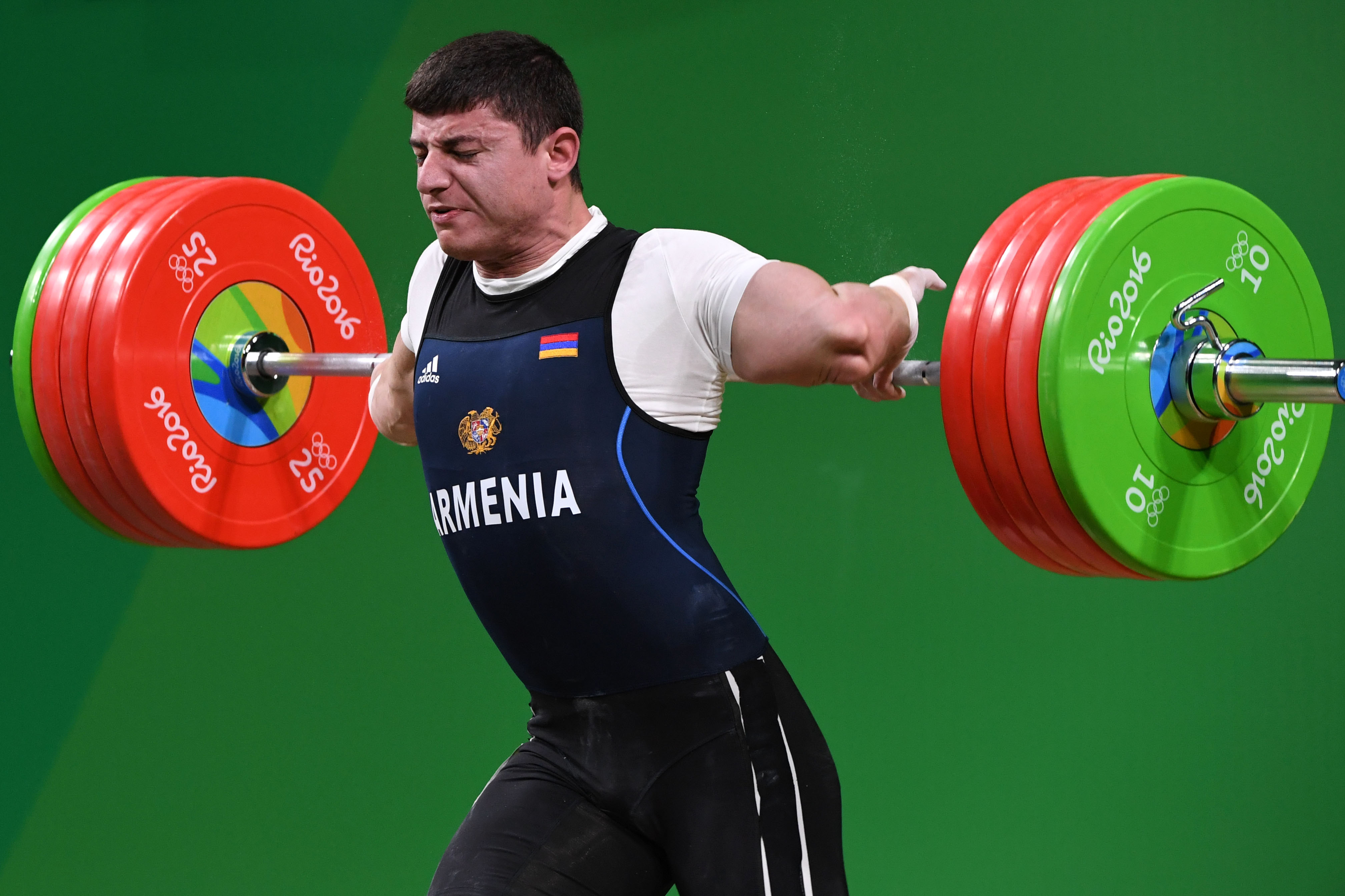 TOPSHOT - Armenia's Andranik Karapetyan sustains an injury while competing during the Men's 77kg weightlifting competition at the Rio 2016 Olympic Games in Rio de Janeiro on August 10, 2016. / AFP PHOTO / GOH Chai Hin