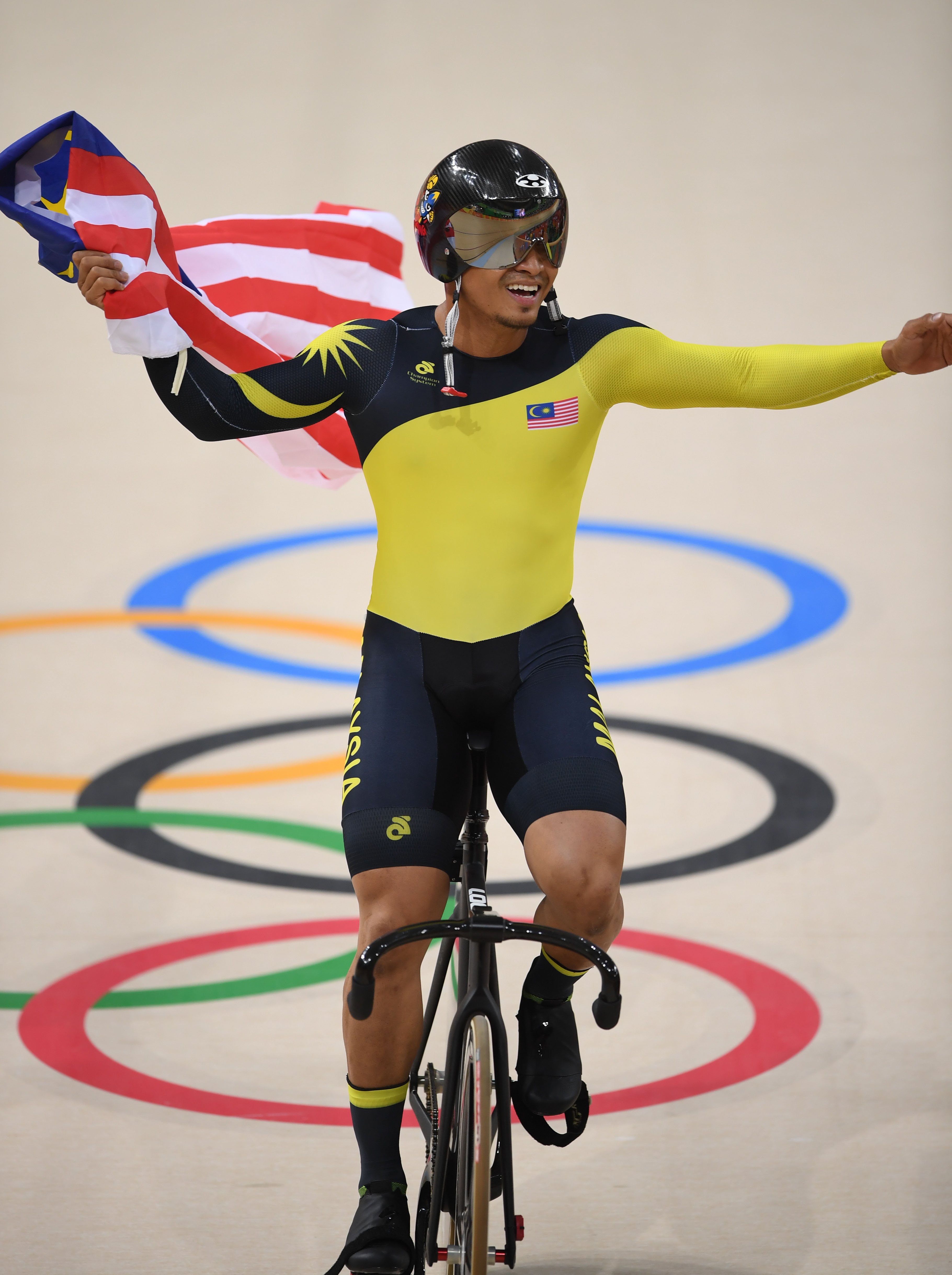 Malaysia's Azizulhasni Awang celebrates with a flag after winning bronze in the Men's Keirin finals track cycling event at the Velodrome during the Rio 2016 Olympic Games in Rio de Janeiro on August 16, 2016. / AFP PHOTO / Eric FEFERBERG