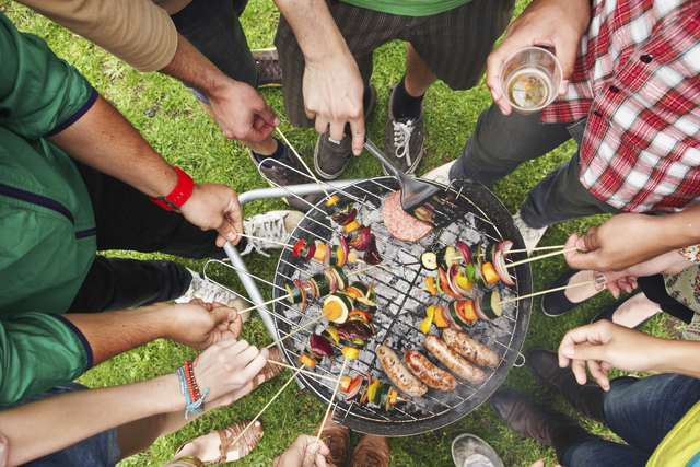 A collection of friends gathered around a bbq