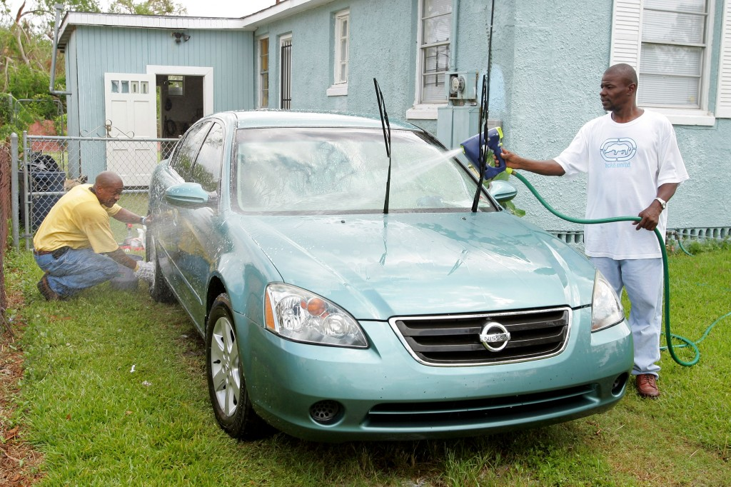 NEW ORLEANS - SEPTEMBER 26: Robert Fulton (L) and Antonio Johnson wash Fulton's car at his home in the Algiers District September 26, 2005 in New Orleans, Louisiana. New Orleans Mayor C. Ray Nagin reopened Algiers to residents. Business owners were allowed into Algiers and several other districts to resume cleanup from Hurricane Katrina that was interrupted when Hurricane Rita passed by the area. (Photo by Ethan Miller/Getty Images)